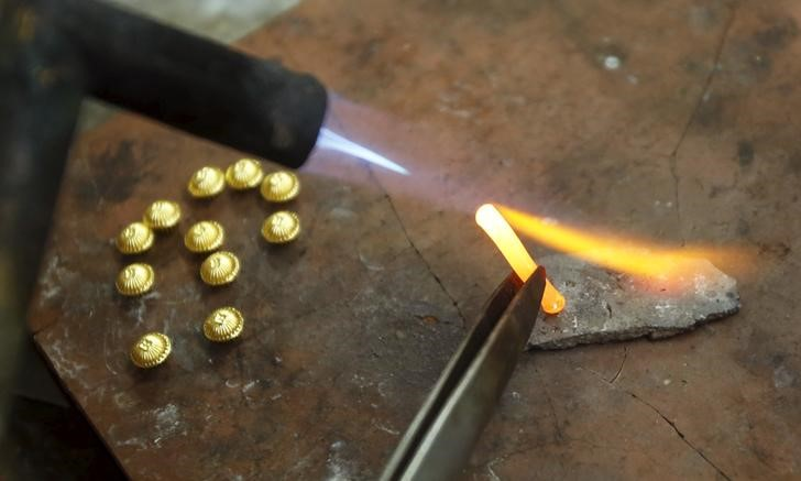 A goldsmith makes products at a shop in Hanoi