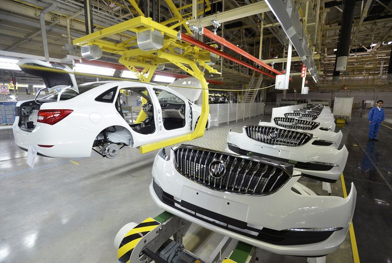 An employee looks on next to an assembly production line of Buick cars at a General Motors factory in Wuhan