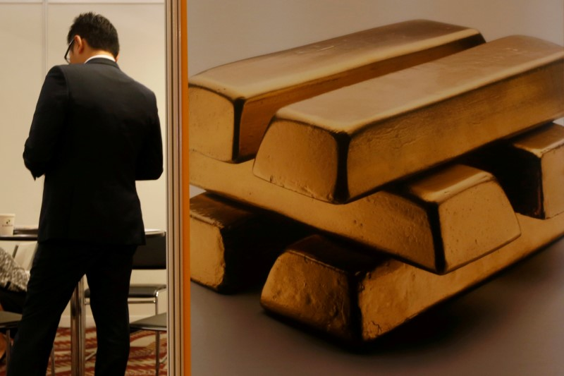 A participant stands beside an illustration of gold at a booth during LME Week Asia in Hong Kong