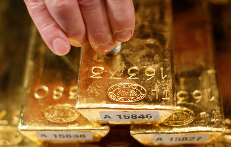 FILE PHOTO: An employee of Deutsche Bundesbank tests a gold bar with an ultrasonic appliance during a news conference in Frankfurt